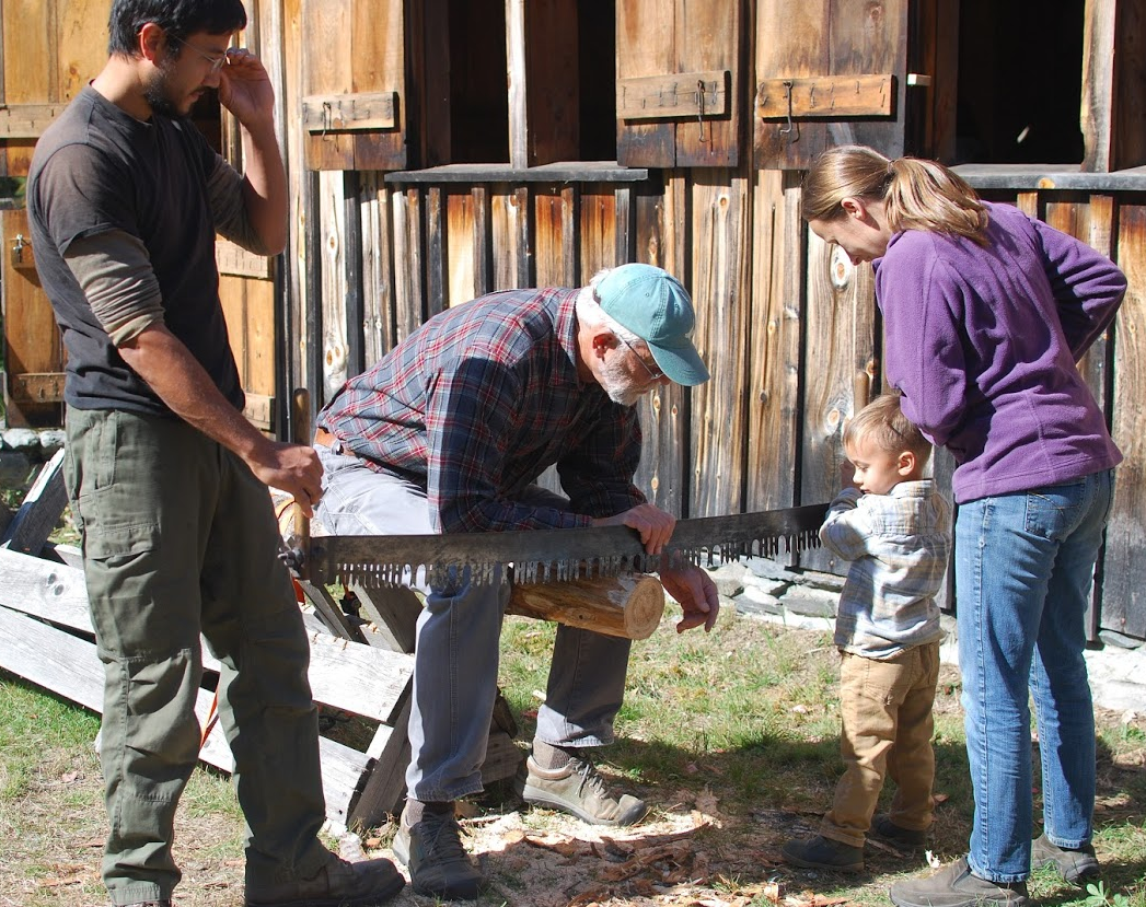 Parents and volunteer helping boy saw log.