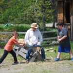 Kids crosscut sawing.